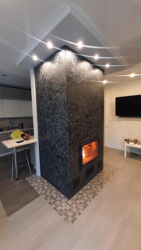 Теплоёмкая печь-камин в красивой, тёмной штукатурке.